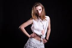 在白色衬衣的皮包骨头的性感的模型在黑背景在演播室 库存照片