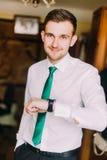 在白色衬衣的年轻英俊的商人有绿色领带的检查时间的看在他的手表 免版税库存图片