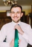 在白色衬衣的年轻英俊的商人穿戴与愉快的微笑的绿色领带在他的面孔 库存照片
