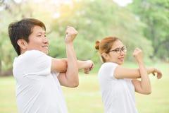 在白色衬衣锻炼的愉快的亚洲夫妇在公园 图库摄影