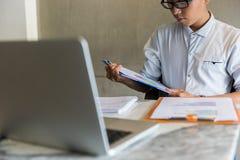 在白色衬衫的商人读财政文件的 免版税图库摄影