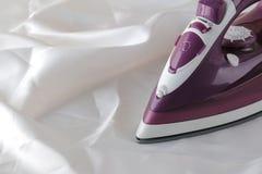 在白色被弄皱的织品片断的淡紫色铁  衣裳电烙 家庭电气用品 免版税库存照片
