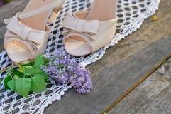 在白色被编织的轨道的婚礼鞋子 库存照片