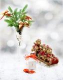 在白色装饰觚、白色礼物盒、红色和金玩具的圣诞树涉及爬犁、糖果和雪 库存图片
