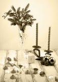 在白色装饰觚、白色礼物盒、蓝色球、烛台有红色蜡烛的和装饰石头的圣诞树 免版税图库摄影