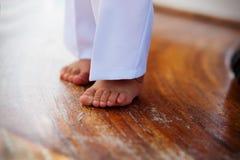 在白色裤子的婴孩腿在一个木地板上 免版税图库摄影