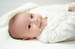在白色身体打扮的逗人喜爱的树月男婴看照相机,当放置在婴孩更换者时 库存图片