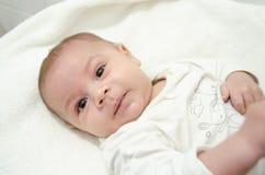 在白色身体打扮的逗人喜爱的树月男婴看照相机,当放置在婴孩更换者时 图库摄影