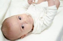 在白色身体打扮的逗人喜爱的树月男婴看照相机,当放置在婴孩更换者时 免版税库存图片