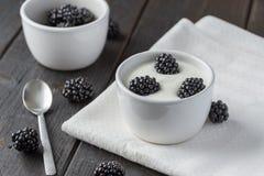 在白色酸奶的黑莓在白色餐巾 免版税库存照片