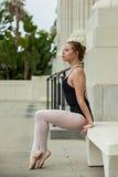 在白色长凳摆在的俏丽的芭蕾女孩 免版税库存照片