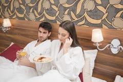 在白色长袍的有吸引力的年轻夫妇,享受食物和饮料 库存照片