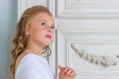 在白色长袍祈祷的一个美好的小女孩天使 免版税库存照片