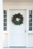 在白色门的绿色圣诞节花圈 免版税库存照片