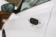 在白色门锁特写镜头的汽车钥匙与拷贝空间 免版税图库摄影