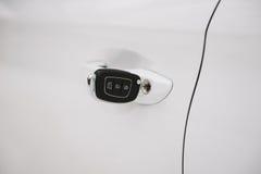 在白色门锁特写镜头的汽车钥匙与拷贝空间 免版税库存照片