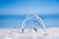 在白色闪烁和蓝色背景的清楚的玻璃心脏 免版税库存照片