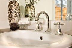 在白色陶瓷做的现代盥洗盆与一弯曲的龙头fixe 库存照片