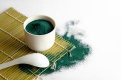 在白色陶瓷容器的Spirulina粉末 库存图片