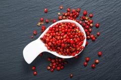 在白色陶瓷杯子的有机桃红色干胡椒 免版税库存照片