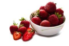 在白色陶瓷碗投入的新鲜的草莓堆和一些草莓在白色桌上传播了 免版税库存照片
