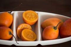 在白色陶瓷碗的树蕃茄在木背景 免版税库存照片