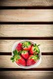 在白色陶瓷碗的草莓在木桌上 库存照片