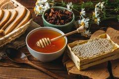 在白色陶瓷碗,蜂蜜滴管匙子,在土气木桌上的自创蜂窝的蜂蜜 免版税图库摄影