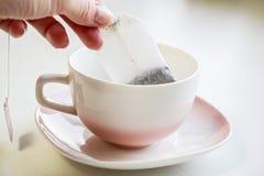 在白色陶瓷茶杯投入的茶包 库存照片