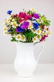 在白色陶瓷水罐的野花 库存图片