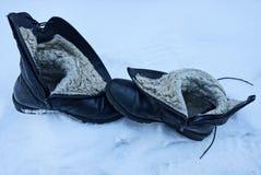 在白色随风飘飞的雪的两只老黑皮靴 免版税图库摄影