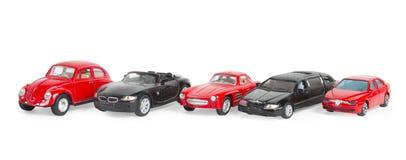 在白色隔绝的五辆减速火箭的红色和黑玩具汽车 免版税库存照片