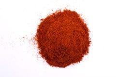 在白色隔绝的堆一粒干燥红色辣椒粉粉末 免版税库存图片