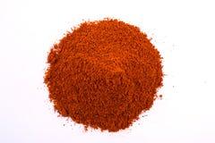 在白色隔绝的堆一粒干燥红辣椒粉末 免版税图库摄影