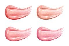 在白色隔绝的套不同的嘴唇光泽淡色污迹样品 被弄脏的构成产品 免版税库存照片