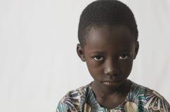 在白色隔绝的恼怒的年轻非洲男孩,显示他的面孔为 图库摄影
