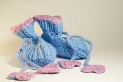 在白色隔绝的手工制造编织的婴孩赃物 免版税库存照片