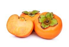 在白色隔绝的整体和一半新鲜的成熟柿子 免版税库存图片