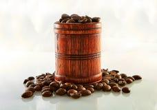 在白色隔绝的木桶的咖啡豆 库存图片