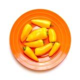 在白色隔绝的橙色板材的黄色胡椒 免版税库存图片