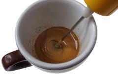 在白色隔绝的速溶咖啡和杯子的电搅打机 免版税库存照片