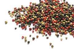 在白色隔绝的黑,红色和白胡椒五谷 香料 食物 图库摄影