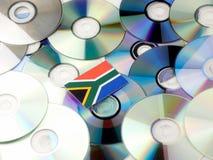 在白色隔绝的CD和DVD堆顶部的南非旗子 免版税库存照片