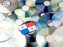 在白色隔绝的CD和DVD堆顶部的巴拿马旗子 免版税库存照片
