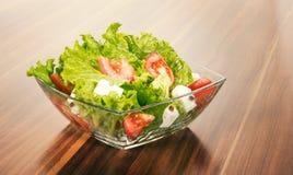 在白色隔绝的一个玻璃碗的混杂的salat。 库存照片