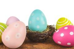 在白色隔绝的一张木桌上的五颜六色的复活节彩蛋 图库摄影