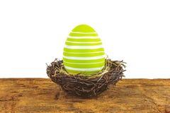 在白色隔绝的一张木桌上的绿色复活节彩蛋 免版税库存照片