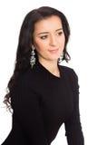 在白色隔绝的一件黑礼服的美丽的深色的女孩 库存照片