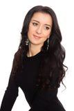 在白色隔绝的一件黑礼服的迷人的深色的女孩 免版税库存照片