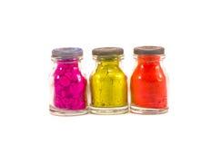 在白色隔绝的三个五颜六色的印地安礼节油漆瓶 库存图片